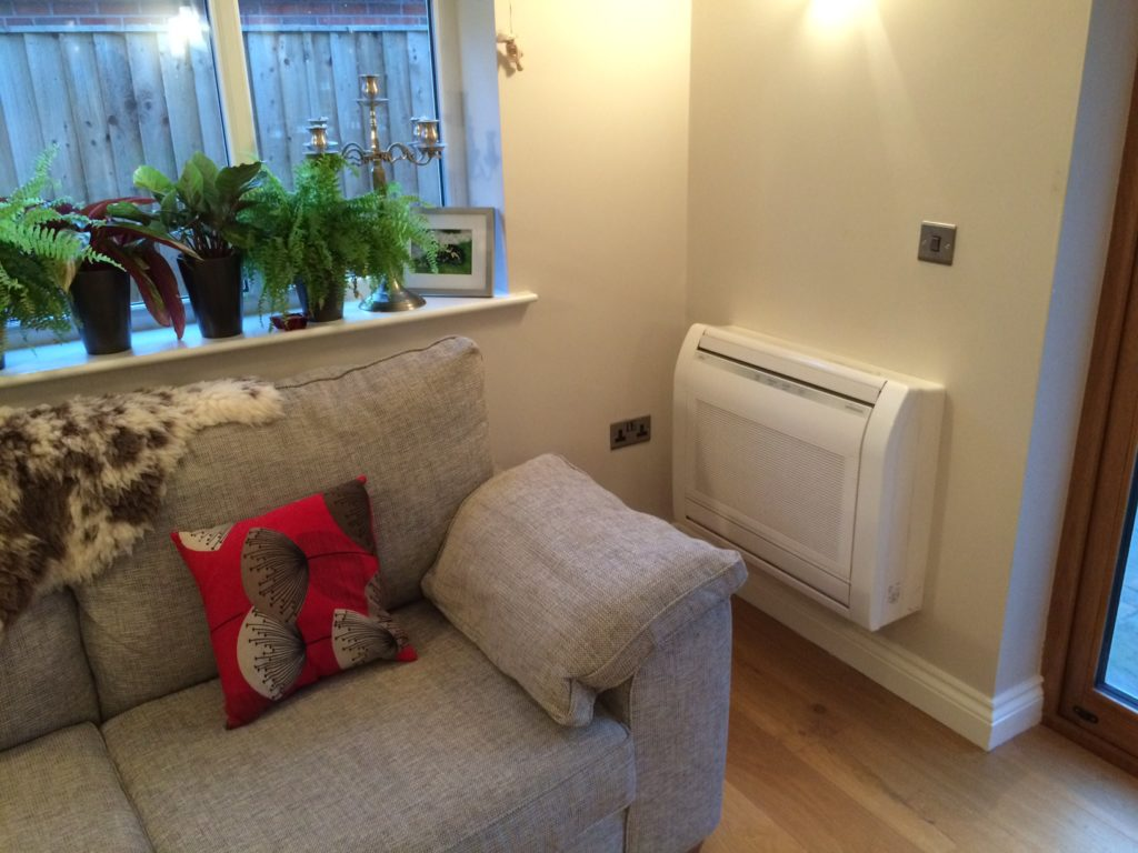 Picture of a heat pump on a wall next to a sofa